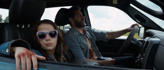 Laura and Logan, from the movie Logan sitting in a car. Laura is a young girl, sitting in the passenger seat wearing novelty sunglasses. Her knuckles are bloody and resting on the car door. Logan, played by Hugh Jackman, is driving and looks to be in pain and covered in blood.