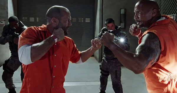 wearing prison orange jumpsuits, Jason Statham (as Ian Shaw) on the left holds up his fist for fights and the Rock (Luke Hobbs) also has his fist raised as if to start a fight. Behind them a man with a lit rifle points his gun at the pair.