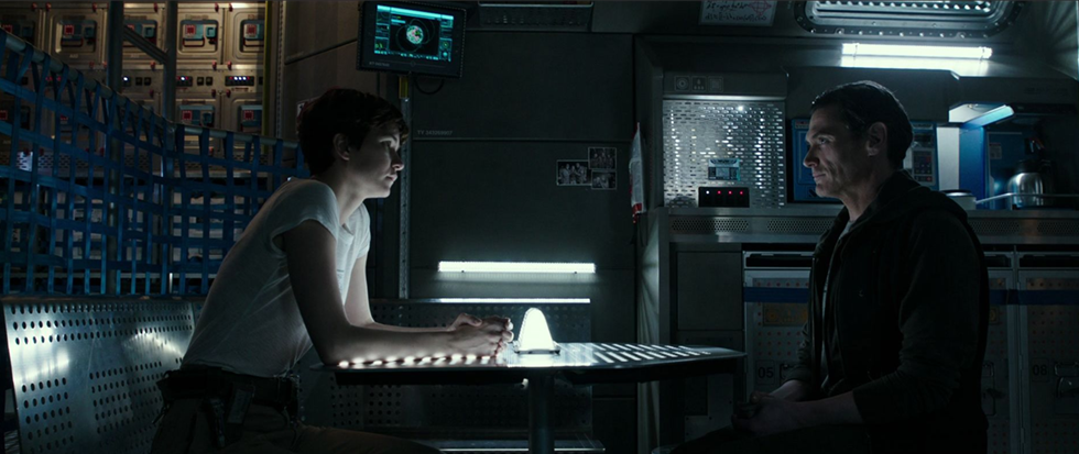 Two people sitting across from each other at a table in a science fiction spaceship. They are Daniels and Oram, characters from Alien: Covenant