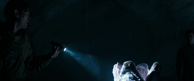 A man with a flashlight points it towards an Alien egg, with another man in the background nearly invisible in the darkness. This is a still from the film Alien Covenant