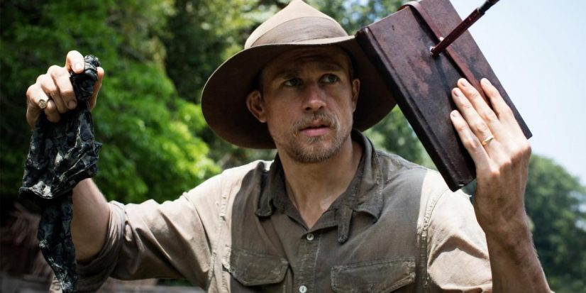 Percy Fawcett (holding a book with an arrow stuck through it) stands looking off screen to the right. This is a still from the film the lost city of z