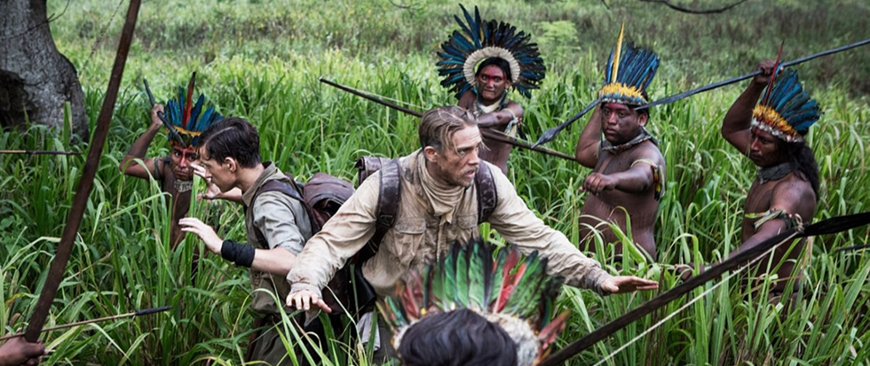 Charlie Hunnam (playing explorer Percy Fawcett) facing off without arms against a bunch of armed indigenous tribesman in a lush green valley. This is a still from the film The Lost city of Z