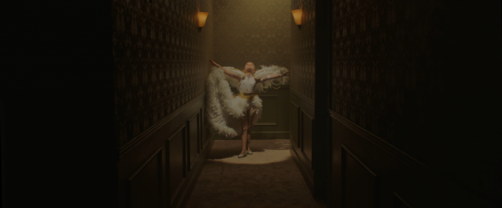 A girl standing at the end of a dark hallway, her body lit in splotlight. She's dressed in a white costume, resplendent in maribou feathers a bit like a Vegas Showgirl. This is a still from the film Casting JonBenet