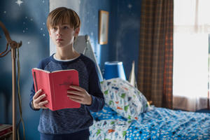 Henry(Jaeden Lieberher) stands off center in a blue bedroom, holding a bright red book open, his expression guarded. This is a still from the movie Book of Henry.