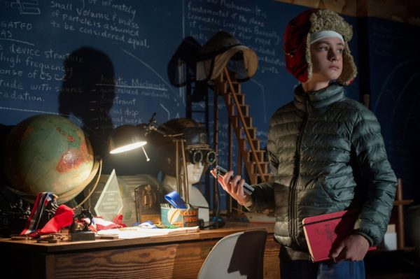 Henry (Jaeden Lieberher) standing off to the right, wearing a puffy jacket and a bandaged head under a hat, looks around a blue room while holding a red notebook. This is a still from the movie the Book of Henry.