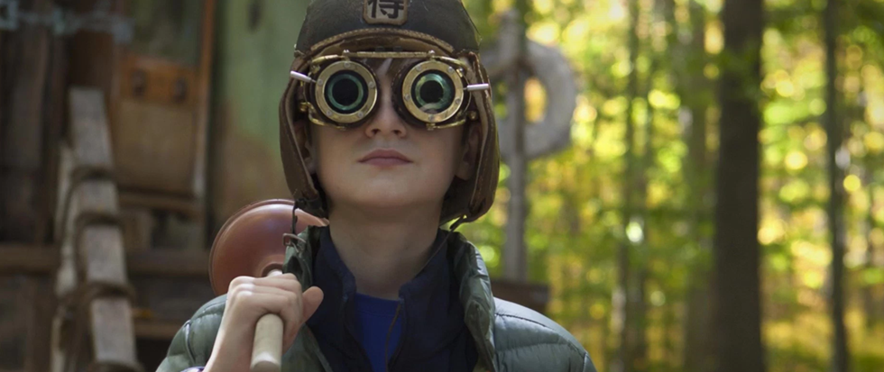 Jaeden Lieberher wearing a pair of steampunky goggles, a flight helmet and with a plunger over his shoulder. This is a still from the movie Book of Henry.