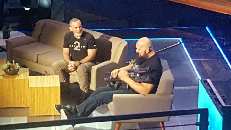 WWE's Big Show, a large man cradling a large gun, interviewing a man in a Destiny 2 t-shirt on a set of couches on a stage.