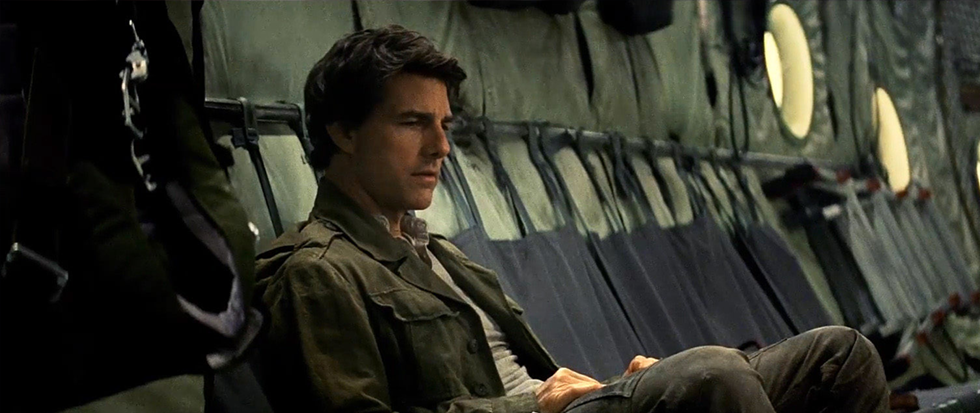 Sitting in a military aircraft, Tom cruise looks real solemn. This is a still from the film The Mummy