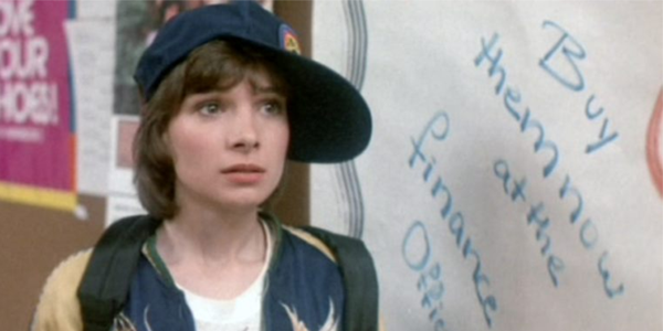 """Paul, with her Nostromo ballcap tilted slightly askew, stands in front of a white board that reads """"buy them now from the finance office."""" This is a still from the film Neon Maniacs"""