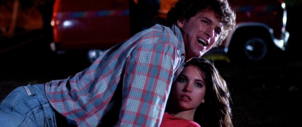 """A """"teenage"""" boy and girl lie on each other, as if caught mid make out. This is a still from the film Neon Maniacs."""