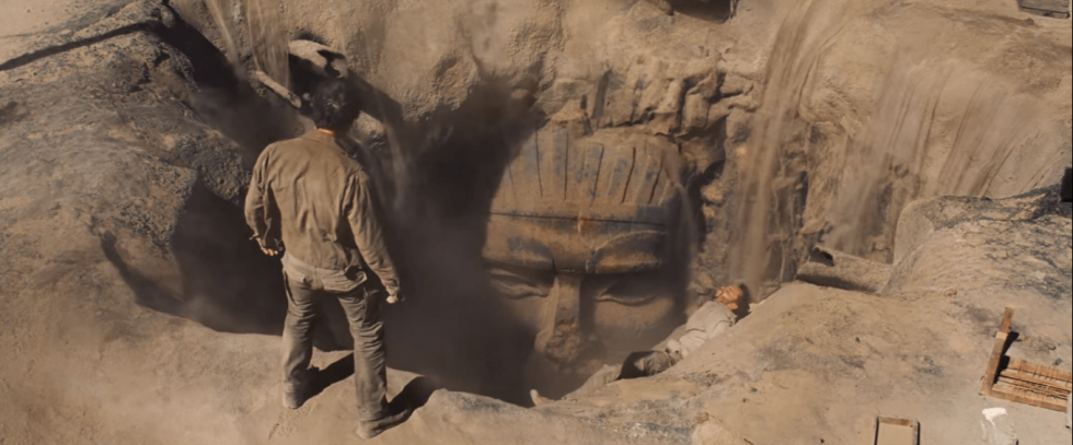 Looking down at a tomb mouth open in the sand. This is a still from the film The Mummy