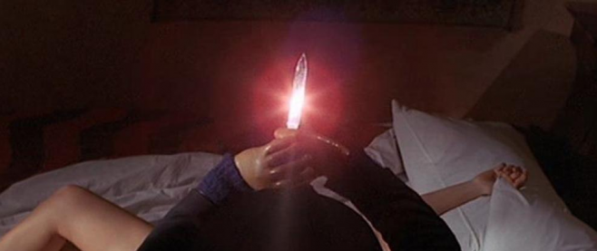 a mans hands hold a knife aloft, the blade lit red in a lens flare. Below him on a bed stretches the naked limbs of a woman. This is a still from the film The Black Belly of the Tarantula.