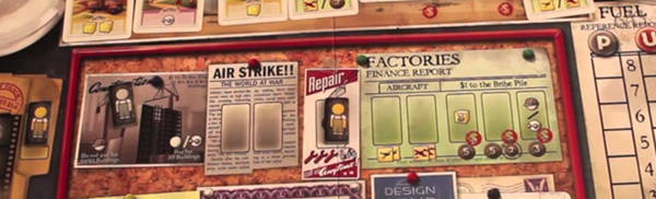"""A close up look at the cards and board from the game the Manhattan Project. The board has a vintage field and the words """"air strike"""" """"factories"""" and """"repair"""" are easily readable."""