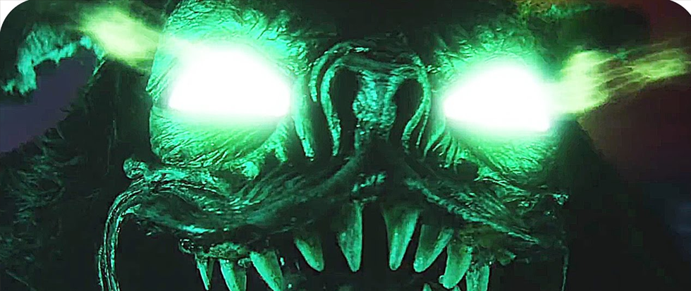 a demonic head with teeth and giant green glowing eyes. This is a still from the Dimension 404 series episode Polybius.