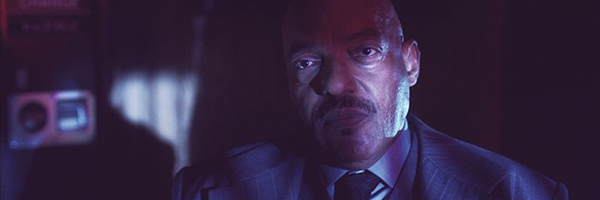 Ken Foree stands in a darkened room, his face half lit as he stares towards the camera. This is a still from the series Dimension 404, episode 4 Polybius.
