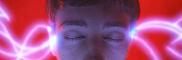 A white teenage boy with his eyes close centers the frame. To his left and right, hitting at his temples, are feathery beams of blue white light. The background is lit an unnerving red. This is a still from the Hulu original series Dimension 404, episode 4 Polybius.