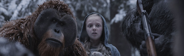 A small blonde girl with an open expression, stands between two armed apes. This is a still from the film War for the Planet of the Apes.