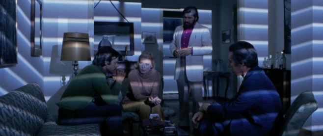 A group of people in a room, looking somber the light across their faces showcasing the lines of a set of near drawn blinds. This is a still from Short Night of Glass Dolls.