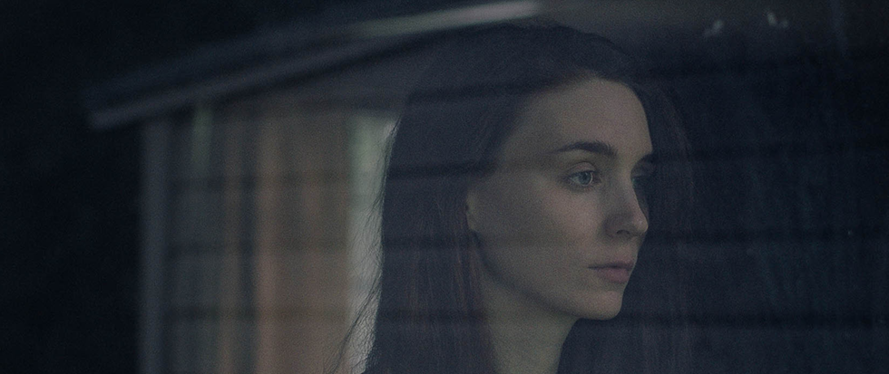 Rooney Mara, a dark haired white woman, stands looking out to the right, as seen through a window. This is a shot from the film Ghost Story.