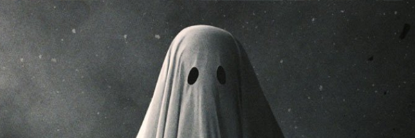 A white sheet ghost stands, it's eyes pointed towards camera, the background a concrete wall. The light is a hard light coming from the left hand side of the frame, the ghost head centered .This is a shot from A Ghost Story.