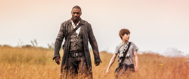 Idris Elba in a long coat and a shoulder holster, walking with a young boy through a yellow brown field. This is a still from the movie the Dark Tower.