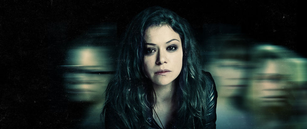 A woman with brunette hair and deep set eyes stands in front of a black background, the women behind her blurred out in motion blur. This is a promotional image for Orphan Black.