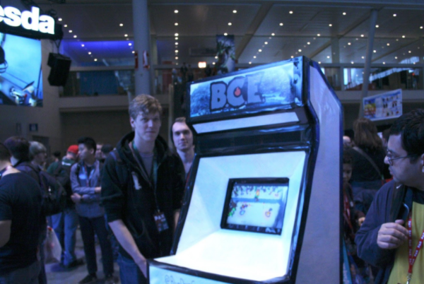 """A white foam board cabinet with a front marquee that reads """"B.C.E"""" in stylized font and an inset touch screen surrounded by a few men in hoodies."""