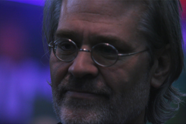 An up close shot of Rand Miller, a white man with tiny circular glasses and some light facial hair, hair slightly longer in the back.