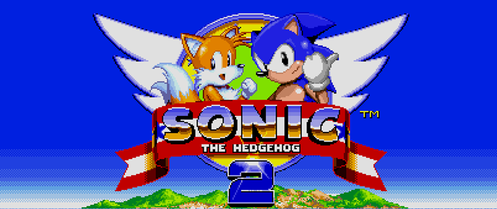 "Tails (a yellow fox like creature with tails) and Sonic (a blue hedgehog with a white mittened fist) pose heroically over a text banner taht reads ""Sonic the Hedgehog 2"""