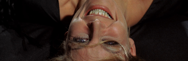 A laughing blonde woman, presented upside down. This is a still from the Lucio Fulci movie A Lizard in a Woman's Skin
