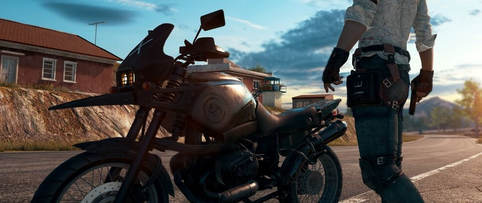 A mans waist highlighted against a silhouetted motorcycle along an empty road. This is a still from Player Unknown's BattleGrounds.