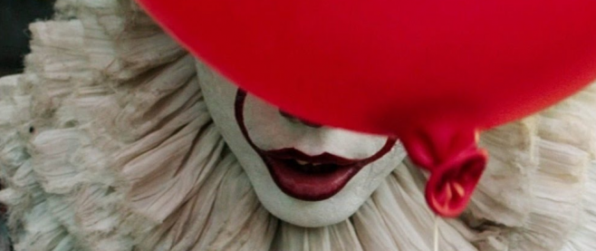 Red lips in a white face with a ruffle behind, a red balloon partially consider the face. This is a still of Pennywise from It.
