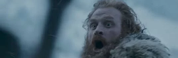 A red haired man with a beard has his mouth open and agape as a character in the foregound attacks him.