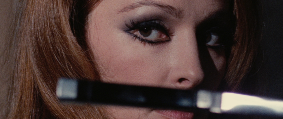 A woman with her eyes heavily rounded in eyeliner, her gaze dark, as a knife sticks out of focus in front of her vision. THis is a still from the film Death Walks in High Heels