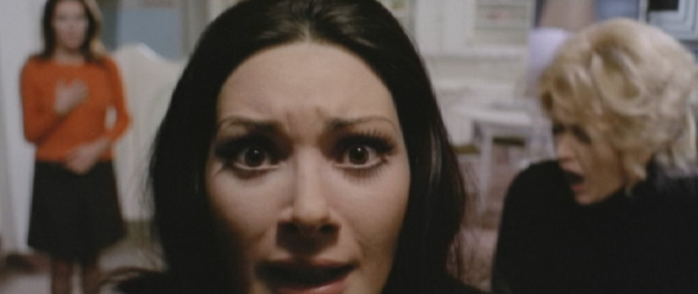 A brunette woman looks at the camera, gaze panicked.