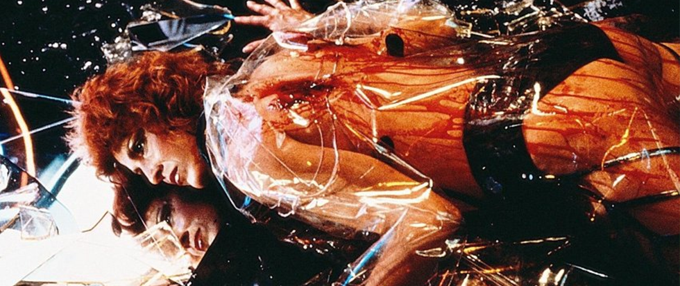 A womans body, in a transparent jacket and black underwear, covered in blood. This is a still from Blade Runner.