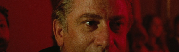 A mans face, older, with his eyes intent and lit in red. This is a still from Death Walks in HIgh Heels.