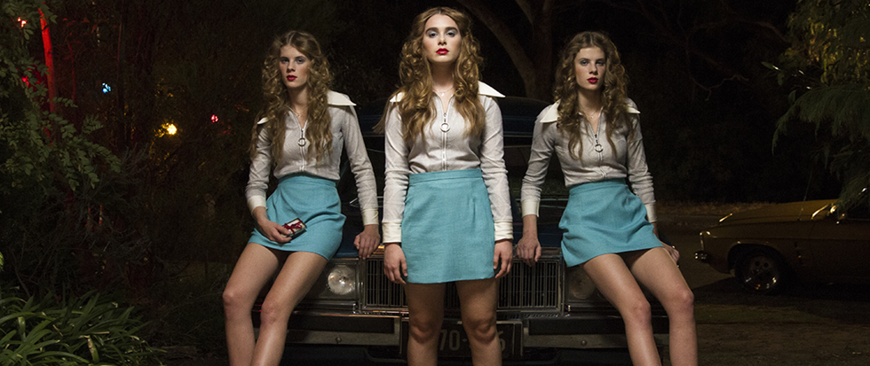 three girls in white shirts and blue skirts leaning against a car.