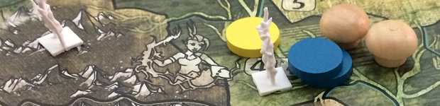 Blue and yellow tokens on a board that depicts island spirits climbing out of the ground. This is a picture of the game Spirit Island.