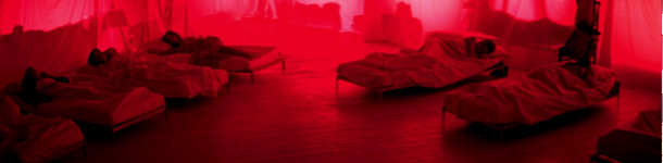 womens beds lit in a deep red glow. This is a still from Suspiria.