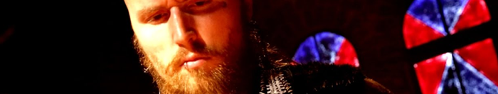 A grim faced white man with a beard, the background a red and blue lit church cloaked in darkness. This is NXT wrestler Aleister Black