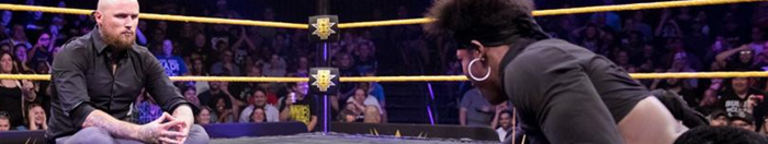 Velveteen Dream, in dark crop top and velvet tights, crawls across the mat towards a seated and cross legged Aleister Black