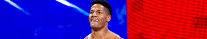 A red and blue background with an African American man (Darren Young) standing in front of it.
