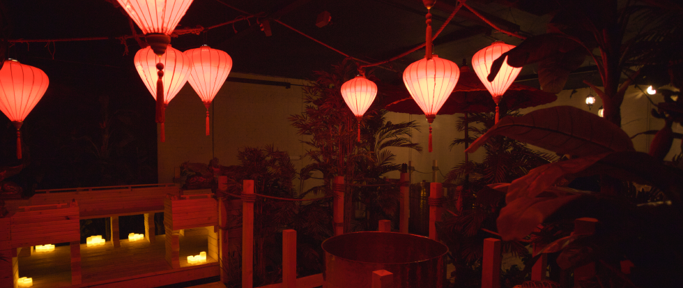 "A photo from inside the Lost Spirits distillery, featuring hanging Asian-inspired lanterns and a dim background. The photo is entitled ""Opium Den"" and is by Dario Griffin"