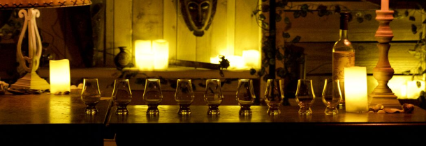 A bunch of small glasses on a dim lit bar. The shot is called Calypso's Room, by Dario Griffin