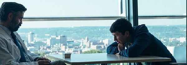 Collin Farrel sits across the table from antagonist Martin, with a city scape behind him.