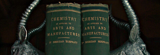 "Two green leather bound books between silverr antlered book ends that reads ""Chemistry as Applied to Arts and Manufactuers"". This photo, though now cropped, was originally taken by Juliet Frew"
