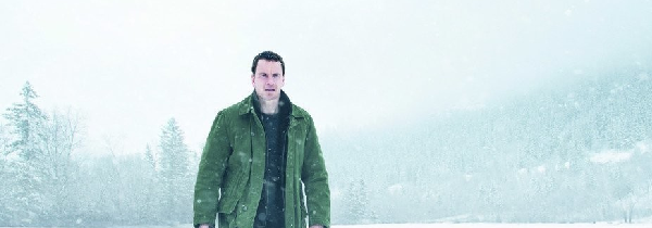 Michael Fassbender, as Harry Hole, walks towards the camera wearing mid level winter gear in a snowy field.