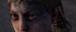 A womans eyes peer out from a blue painted face, her hair running in locs behind her head. This is a still from Hellblade; Senua's Sacrifice