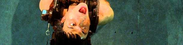 A white man in a black vest yells in pain towards the ceiling. This is a still from Saw 2.